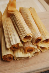 Chicken Tamales rolled in corn husks in a stack