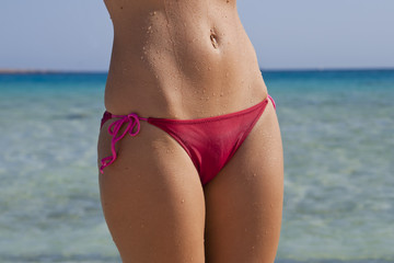 The body of a beautiful woman in a red swimsuit.