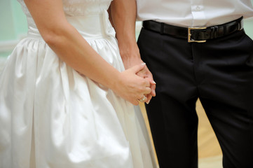 Bride and groom are holding each other's hands at wedding