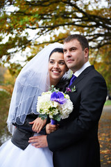 Joyful bride and groom in autumn park