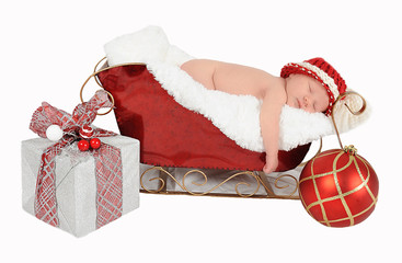 sweet newborn asleep in santa sleigh. isolated