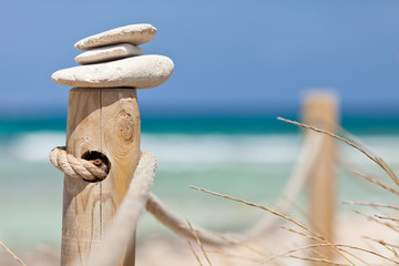 Stones balanced on wooden banister near the beach.