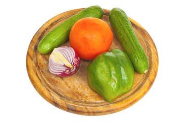 Pepper, onion, cucumber and tomato on a desk