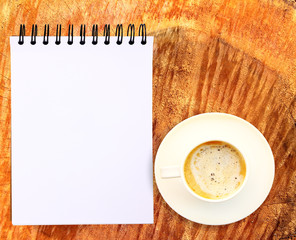 Blank paper tablet with coffee cup on wood background