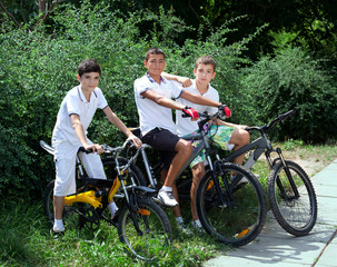 thee teenage friends riding bicycles outdoors