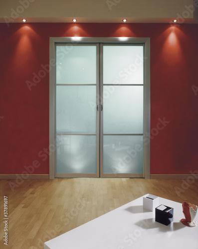 porta a vetri in soggiorno su parete rossa\
