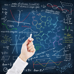Hand writing science formulas on chalkboard