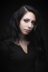 Young attractive gothic brunette woman over black