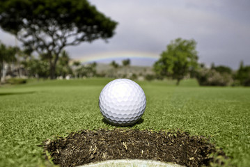 Golf ball at hole.  Rainbow and trees in the background.