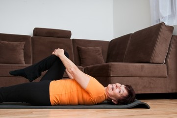 Mature fitness woman exercising at home