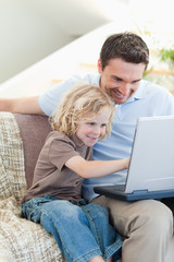 Father and son with notebook on sofa