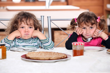 Two grumpy toddlers waiting for their pancakes