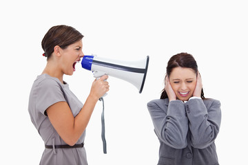 Businesswoman yelling at colleague with megaphone