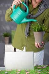 Man watering green plant at home