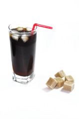 Glass of cola soda drink with sugar cubes