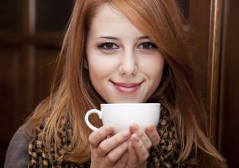 Style redhead girl drinking coffee near wood doors.