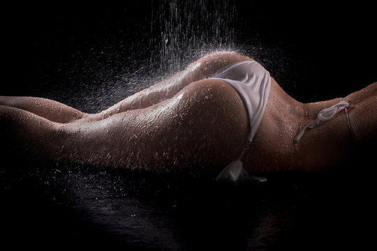 Sexy woman butts under shower, black background