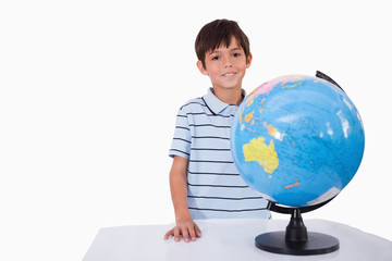 Smiling boy posing with a globe