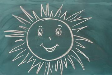 Blackboard with drawing smiling sun closeup