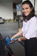 Frau tankt Auto auf Tankstelle auf