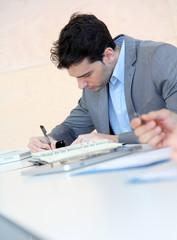 Jeune homme signant un contrat