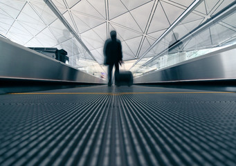 Man rushing through an escalator in  the airport