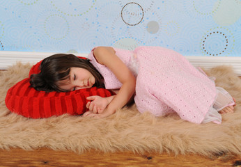 sweet little girl asleep on heart shaped pillow