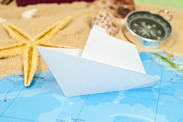 Weltkarte mit Papierschiff, Kompass, Seestern und Sand