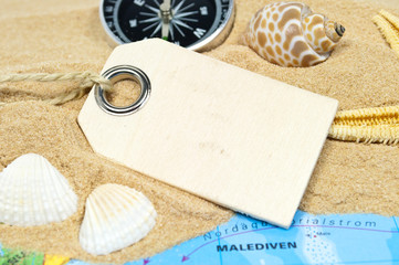 Holzanhänger mit Sand, Muscheln, Seestern und Weltkarte