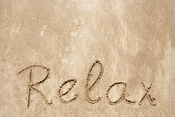 Relax handwritten in sand on a beach