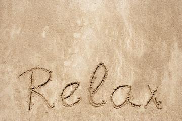 Relax handwritten in sand on a beach
