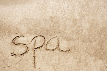 Spa handwritten in sand on a beach