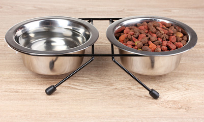 Dry cat food and water in bowls on wooden background