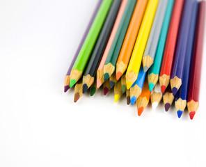 Multi colored pencils in a corner on a white background