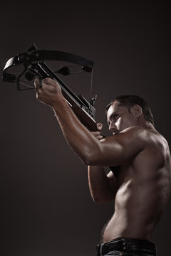 portrait of athletic young man with crossbow