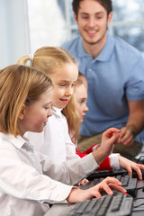 Girls using computers in class with teacher