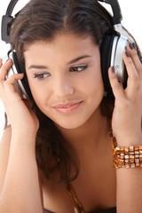 Pretty woman listening music through headphones