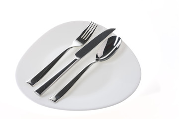 Fork, spoon and  knife on a plate over white