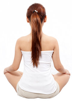 woman meditating taken from behind