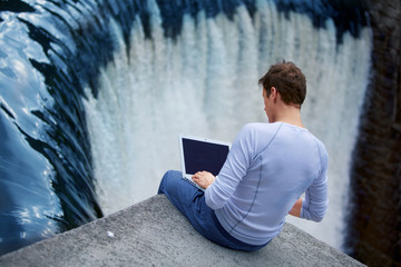 Man with notebook sitting over the waterfall