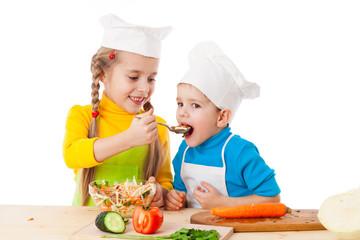 Two kids eating salad