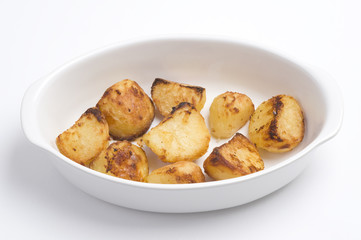 roasted potatoes in a white oven dish