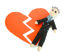 Voodoo doll boy-groom on the broken heart isolated on white