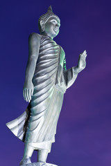 Back of walking Buddha statue in twilight tilted