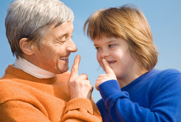 A girl with Down syndrome and her grandmother whispering