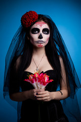 Serious woman in skull face art mask and flowers