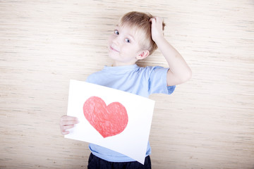 little boy with a picture drawn by heart