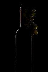 bottle of wine and a bunch of grapes on a black background