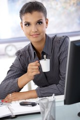 Beautiful businesswoman drinking coffee smiling