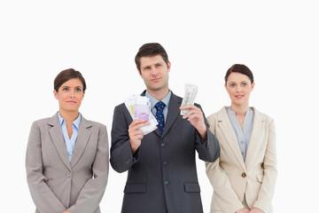 Businessman with money standing between employees